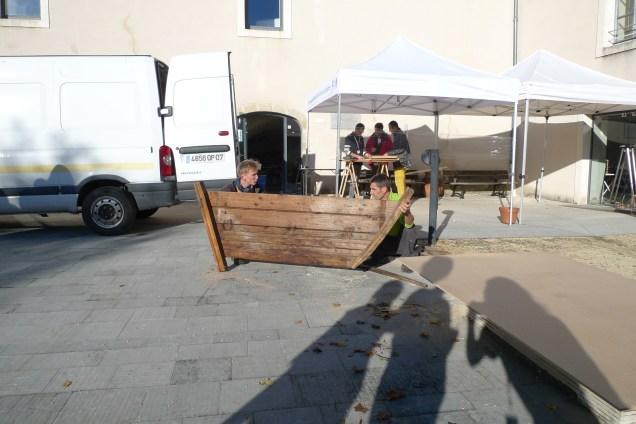 Les participants construisent une barque dans la cour