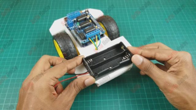 Now, glue the battery holder as follows. After, connect it to the motor driver shield.