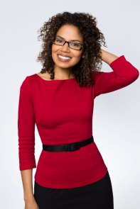 Portrait of woman with curly hair and glasses.