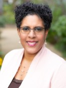 Realtor with glasses in headshot in a a park during a Premium headshot session.