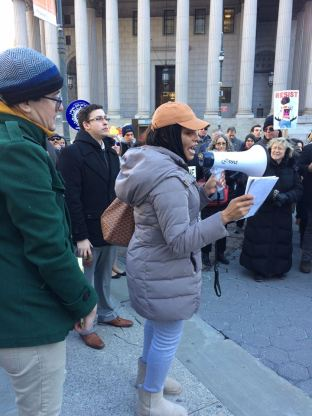 SRLP Movement Building Team member, Kimberly McKenzie, speaks out at the #LawStrikesBack rally. She is holding a megaphone is her hand and is standing in a crowd of protesters.
