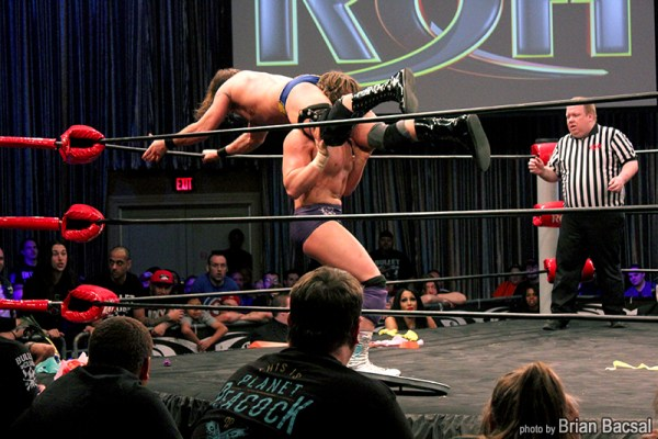 Dalton Castle throws Silas Young over the top rope onto a table below in a Fight Without Honor match