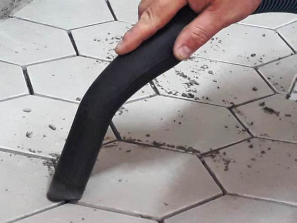 removing loose dry bits of tile adhesive in preparation for grout