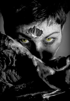 A black and white photograph of a women with hair and glowing yellow eyes. The skin is cracked and a section of forehead has crumbled away to reveal organic looking strands within..