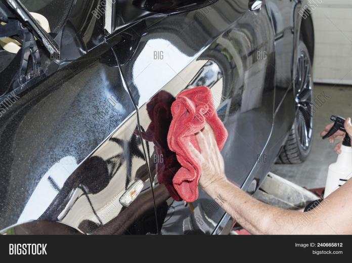 ▷ a man cleaning car with microfiber cloth, car detailing or