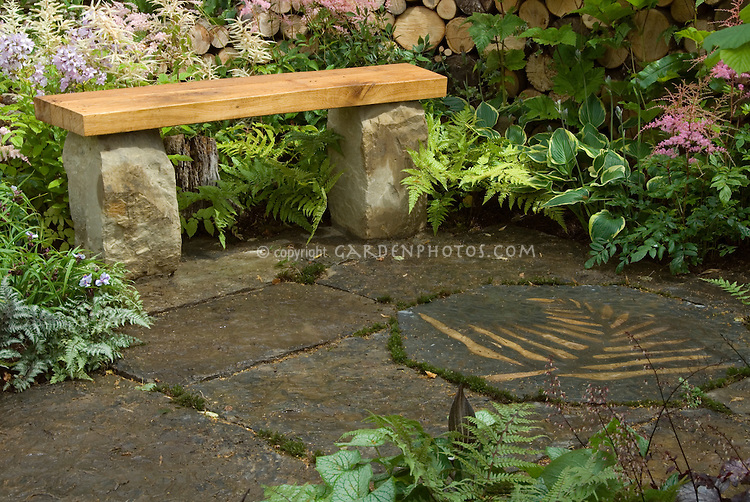 Wooden And Stone Garden Bench On Stone Patio With Leaf
