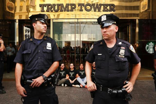 Protesters block the entrance to Trump Tower in Manhattan before being arrested on August 31, 2016 in New York City. The action, called hecho por inmigrantes, or built by immigrants, was intended to draw attention to Republican presidential nominee Donald Trump's immigration policies on the day he is set to give a major speech on immigration in Arizona. The protesters stressed that immigrants were involved in the building of Trump Tower. Trump has previously vowed to deport undocumented immigrants if elected