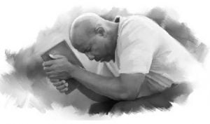 Man Praying with Bible in Hands