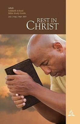 Man Praying While Holding Bible