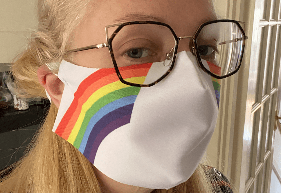 A 34 year old woman wears a face mask emblazoned with a rainbow design