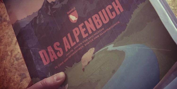 Hand hält Andruck des Alpenbuchs