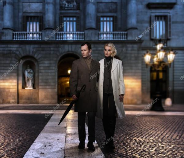 Элегантная пара в пальто против фасада здания вечером ...