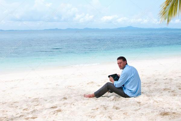 Бизнесмен, сидящий и работающий на пляже с планшетным ...