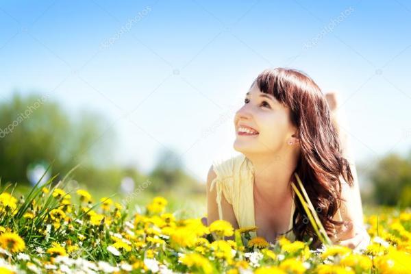 Женщина лежа на траве полный весенних цветов Стоковое