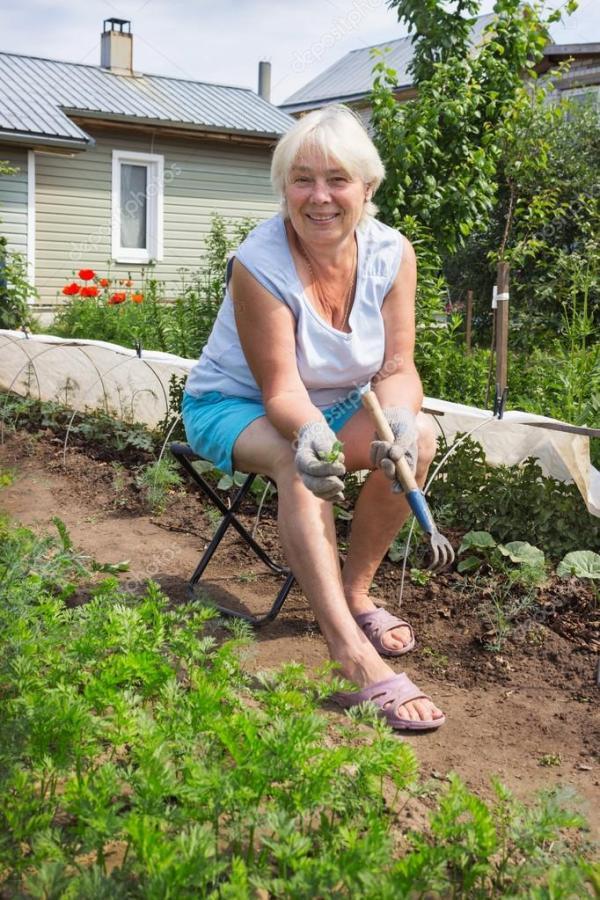 Пожилая женщина удаляет сорняки в саду — Стоковое фото ...