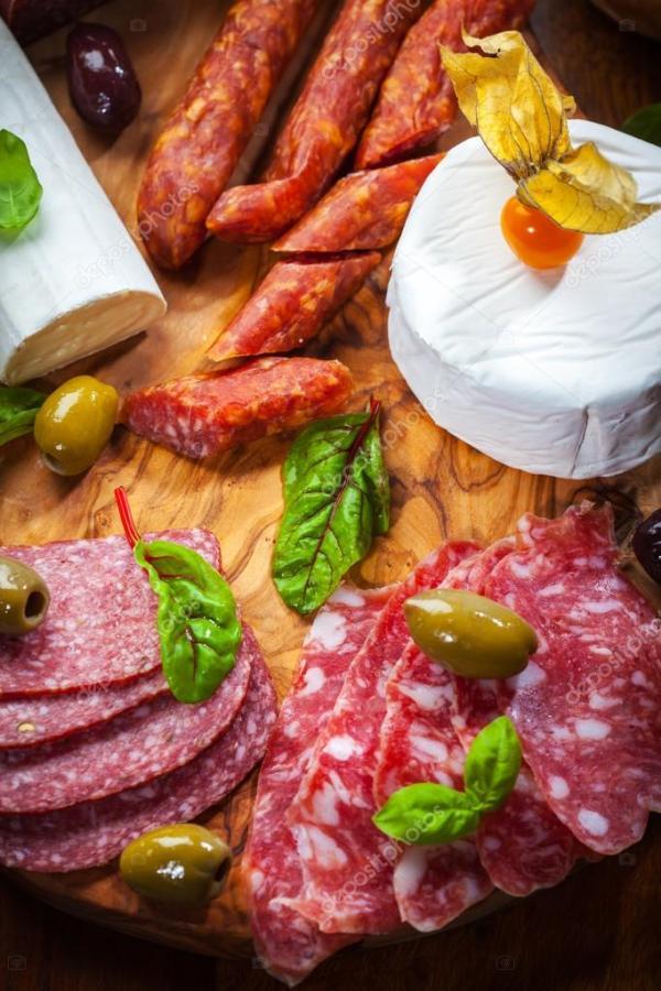 Блюдо антипасто с различными продуктами из мяса и сыра ...