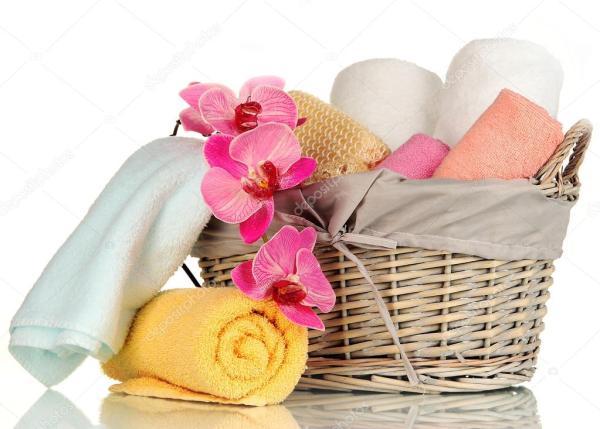Туалетные полотенца сложены в плетеную корзину изолированы ...
