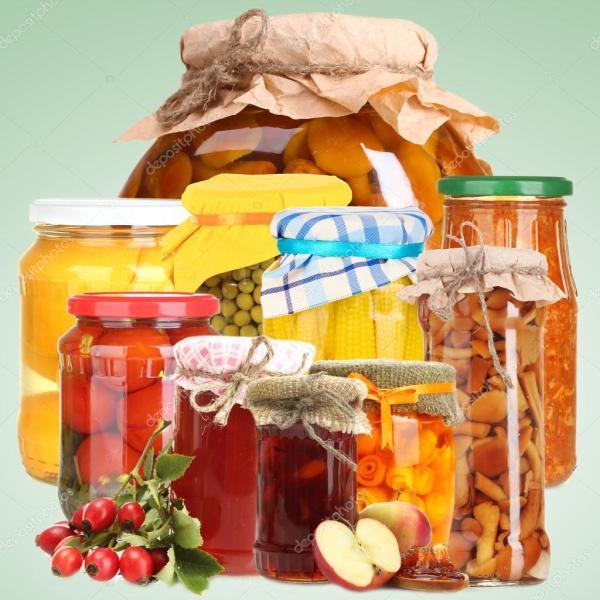 Набор консервированных овощей и фруктов на зеленом фоне ...