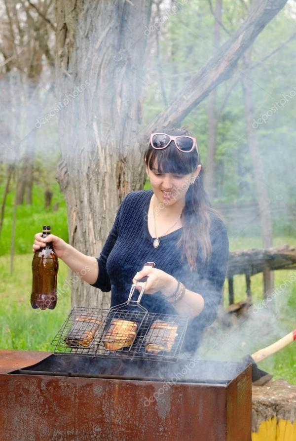 Улыбающаяся женщина готовит на открытом воздухе над ...