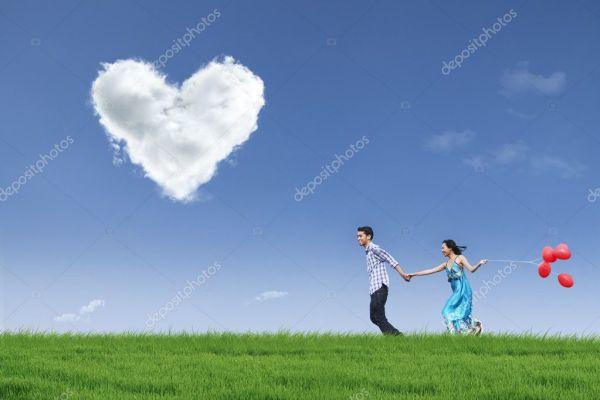 Счастливая пара работает в области с воздушными шарами ...