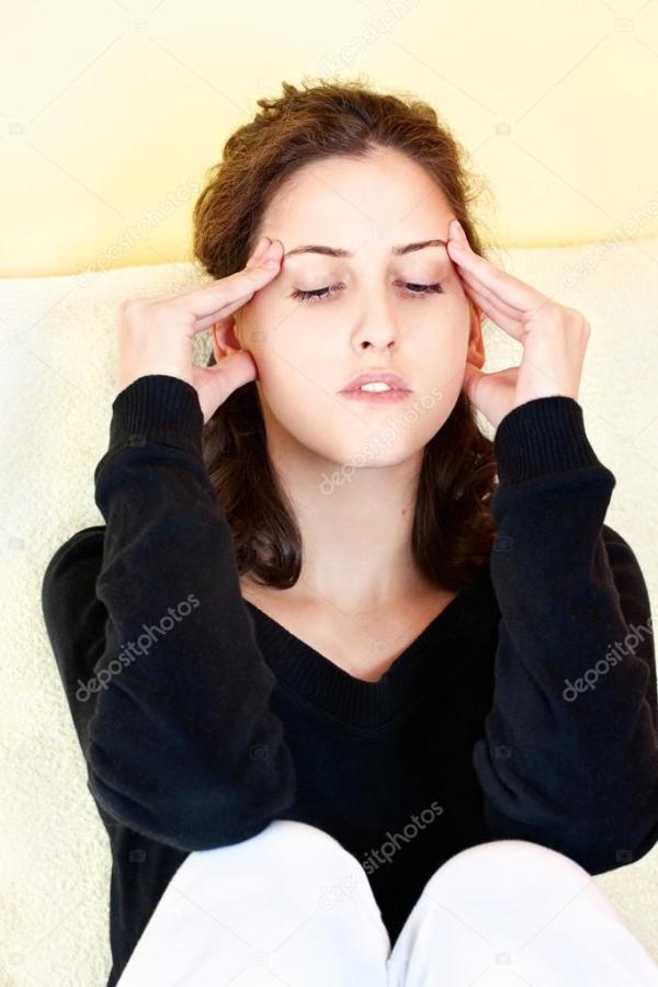 Женщина имеющая головной боли у себя дома