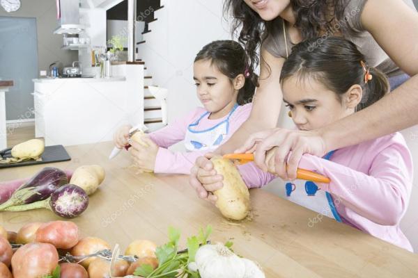 Фото чистка картошки. Молодая мама учит дочерей близнецов ...
