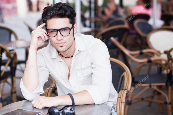 Привлекательный мужчина в очках, стоя на террасе с видом ...