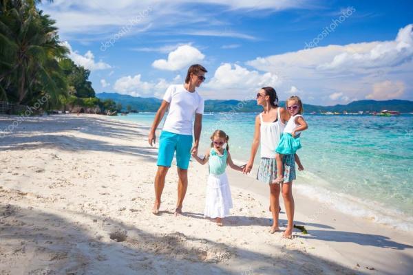 Молодая красивая семья с двумя детьми на тропический отдых ...
