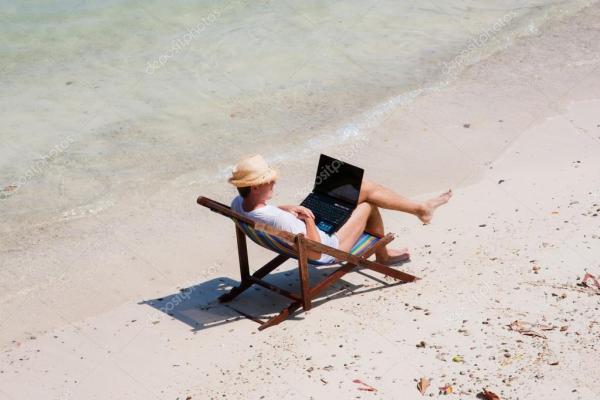 Мужчина сидит на шезлонге с ноутбуком на пляже — Стоковое ...