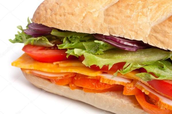 длинный багет бутерброд с салатом, ломтиками свежих овощей ...