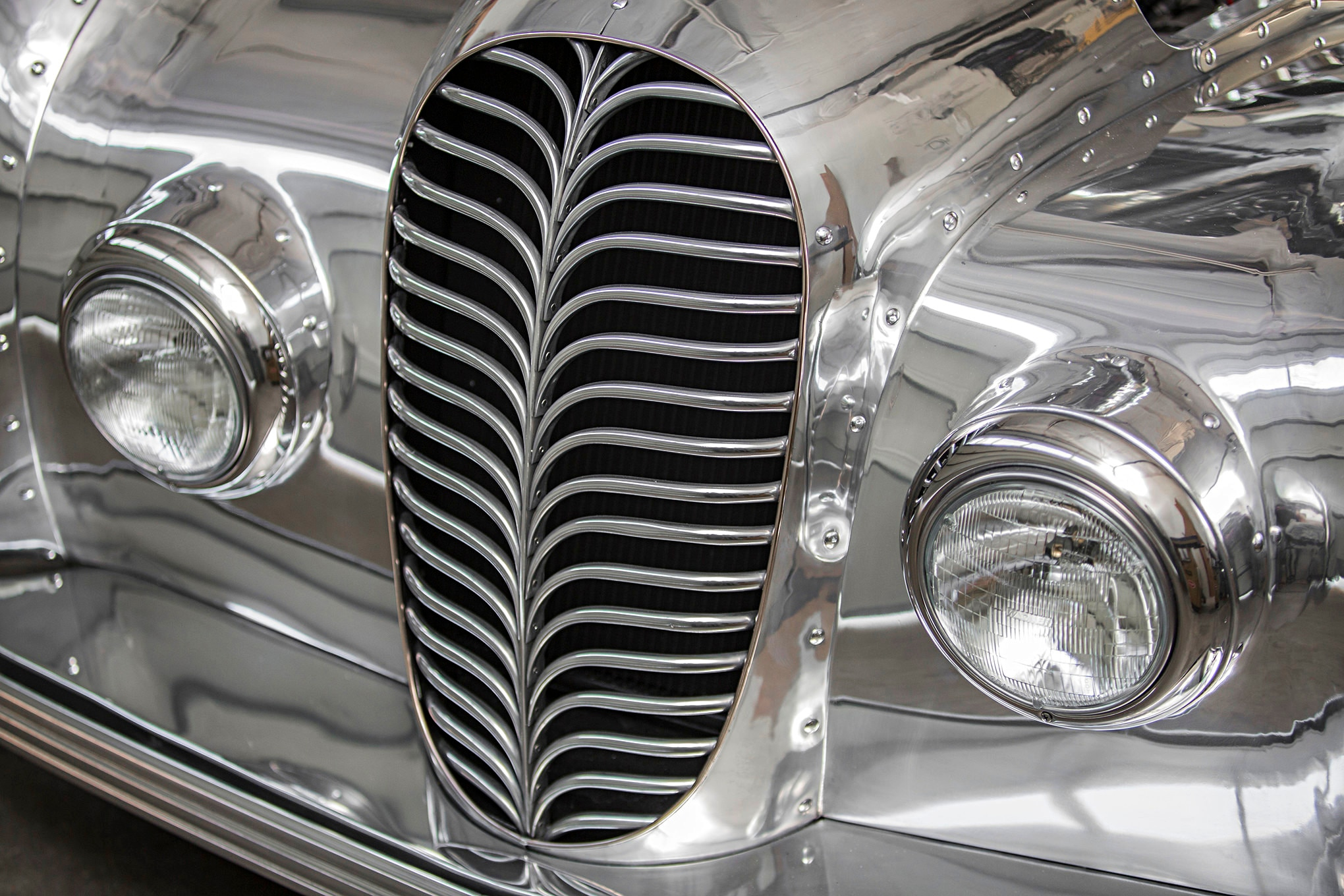 Initially Randy thought a horizontal grille, like the one employed by the Delahaye 145, was the way to go on the Dodici. An initial mockup showed that the grille needed a bit more substance. A vase provided the inspiration Randy needed. The pattern on the vase resembled a feather, and was made by pulling a set of horizontal lines downward with a perpendicular brushstroke. To duplicate the look, randy used a remarkably simple round form mounted in his bench vise, which simultaneously crimped the end of the aluminum tube and gave it a smooth radius 90-degree bend.