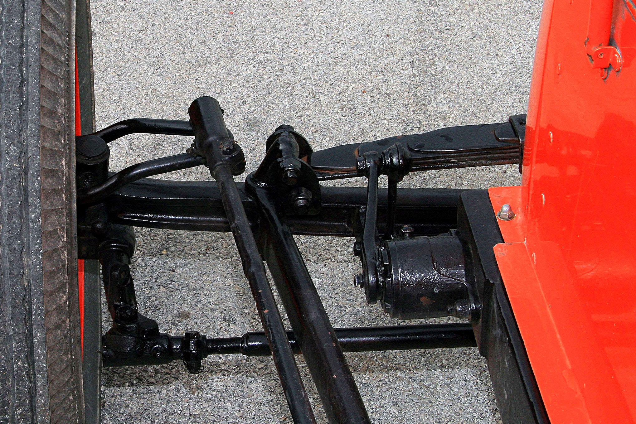 This is a view of the left-front suspension set-up. Visible in this photo is the steering rod which is controlled by the driver. The upper-arching leaf spring carries four leafs.