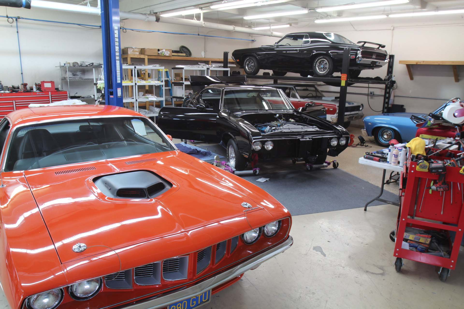 """This 1971 'Cuda is Ken's personal car. He found it on eBay needing precious little work to make it nice. """"I buffed the paint!"""" Ken joked, sounding a little relieved that this car didn't need a ton of bodywork. Its interesting combination of options is what makes the car unique: the 'Cuda has a 340 engine with a N96 Shaker hood, rear wing, and the billboard sticker package. To that, Ken added Control Freaks' front coilover suspension conversion. Ken also rebuilt the engine, turning it into a stealthy-looking 408 with Wiseco pistons and a hydraulic roller cam conversion."""