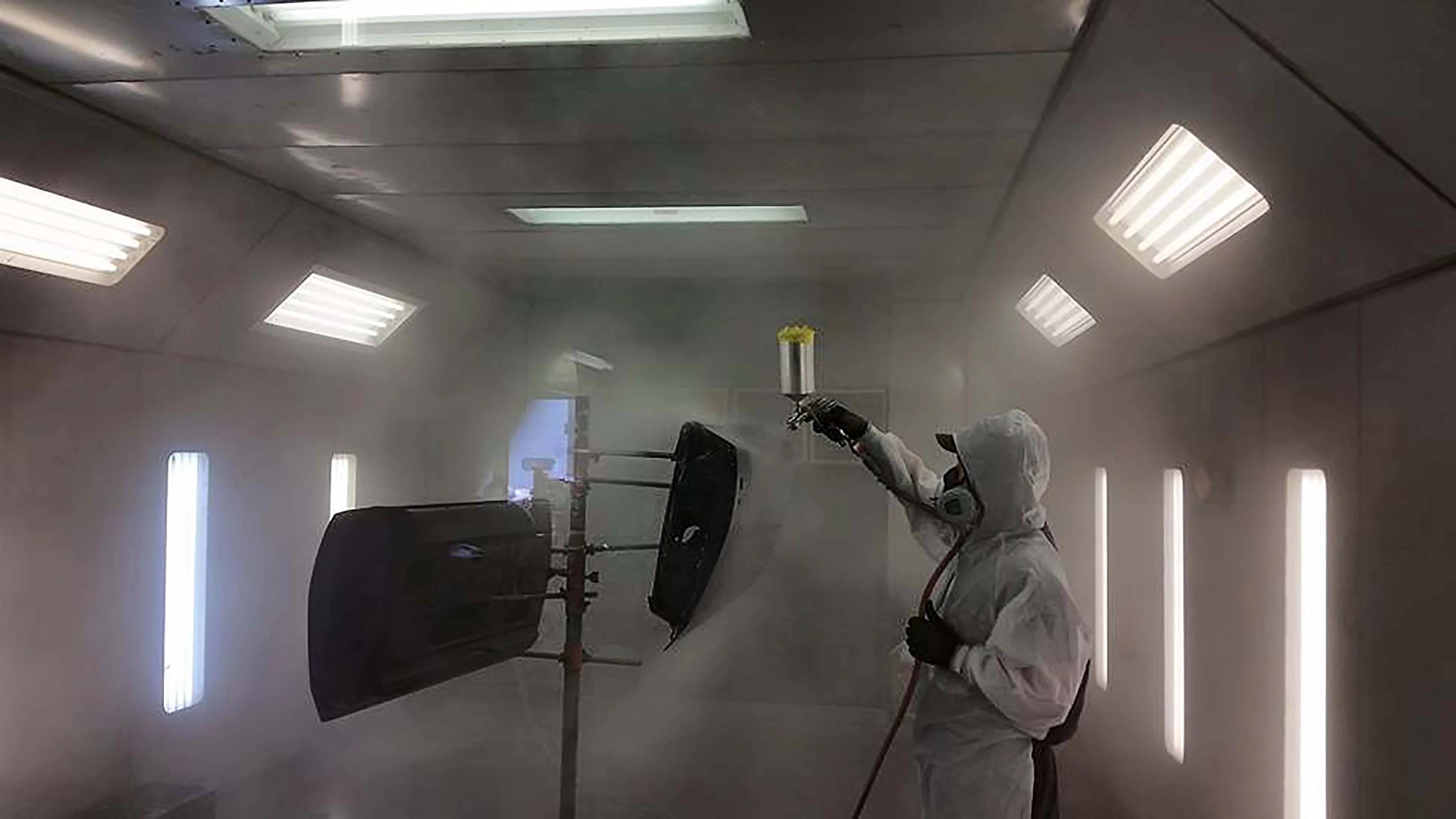 A cloud of spray fills the paint booth as Webb applies the last coat of the Axalta Chromapremier.