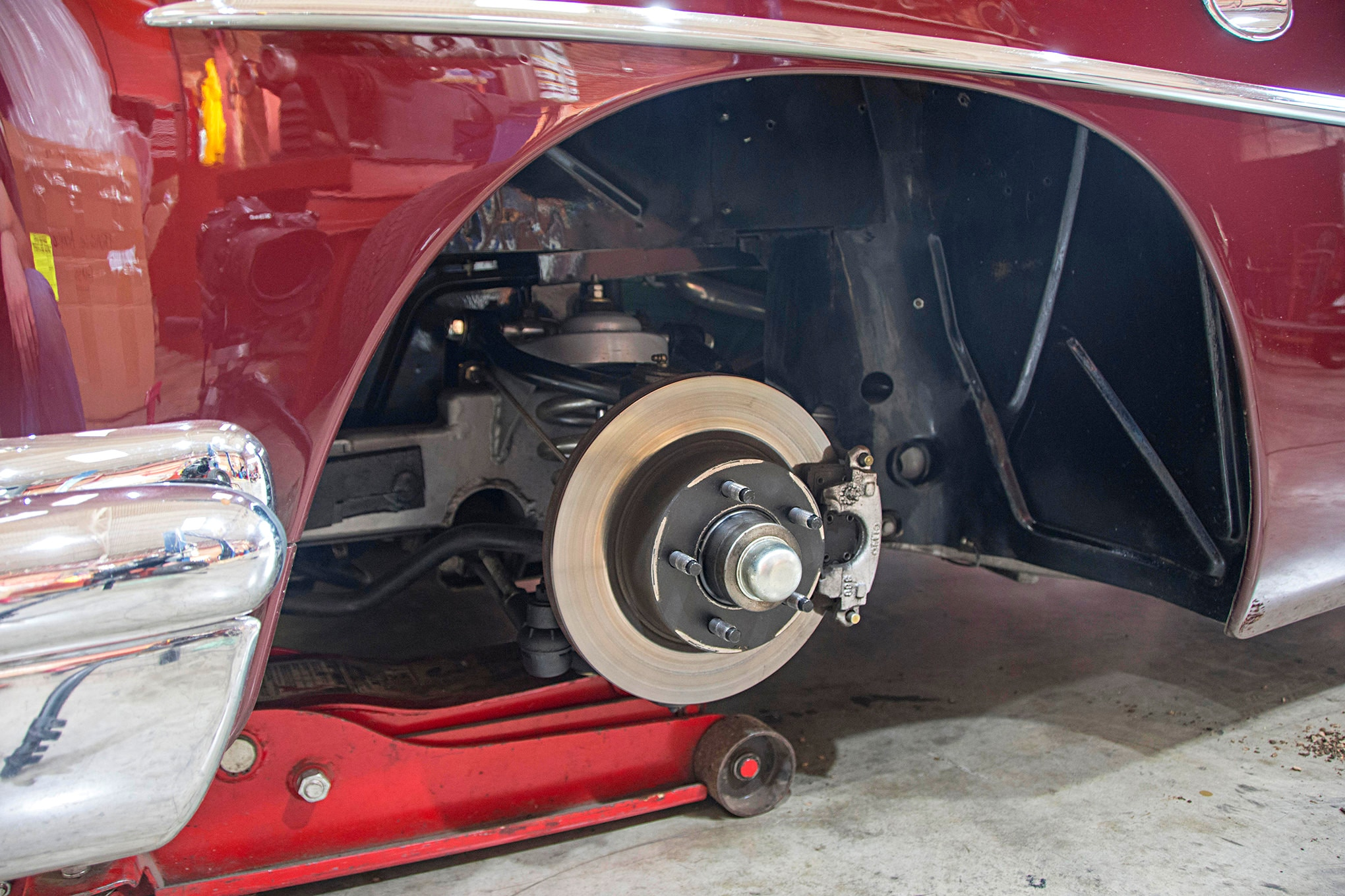Our subject is a 1954 Buick, which features a Mustang II front suspension with GM-style disc brakes. Some cars have drastically different track widths when comparing drum brakes to disc brake conversions, so always take that into consideration. When measuring for tire and wheel fitment, always do so with the car at ride height. We place the jack beneath the lower control arm.
