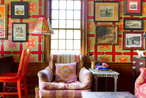 sofá listrado, papel de parede geométrico e cadeira vermelha na biblioteca
