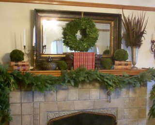 A wreath paired with candles and potted plants.
