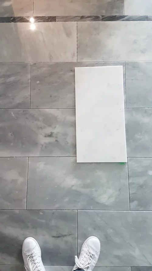 white marble tile turned gray after install