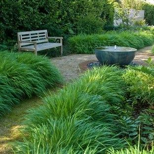 This is an example of a mid-sized victorian backyard partial sun garden for summer in Sussex with a garden path and gravel.
