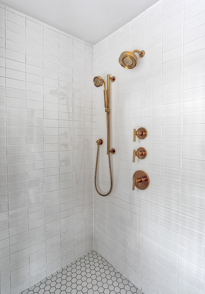 white subway tile shower with brass