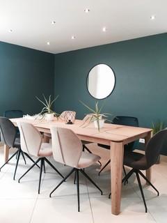 salle a manger avec un mur vert