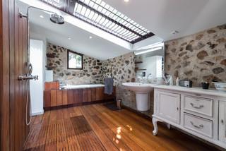 salle de bain avec un sol en bois fonce