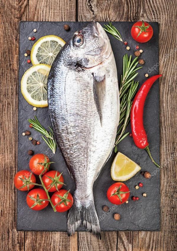 Свежая рыба, лимон, специи и помидоры черри на каменной ...