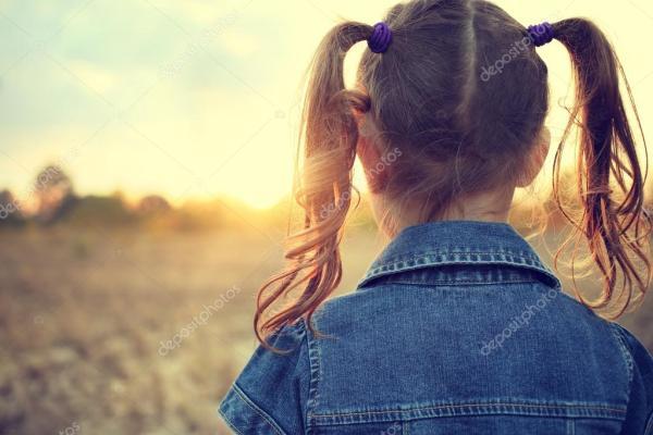 Девочка в шнурках, смотрящих на солнце вечером на лугу ...