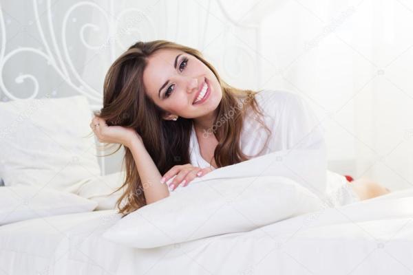 Девушка сидит на подушке. Красивая девушка лежит в белой ...