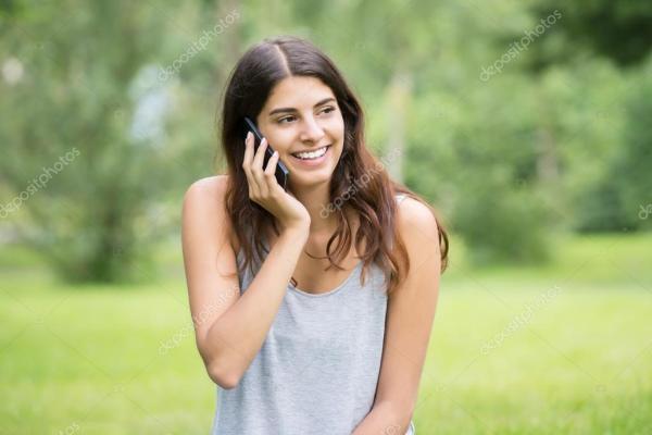 Улыбается женщина говорить на мобильном телефоне ...