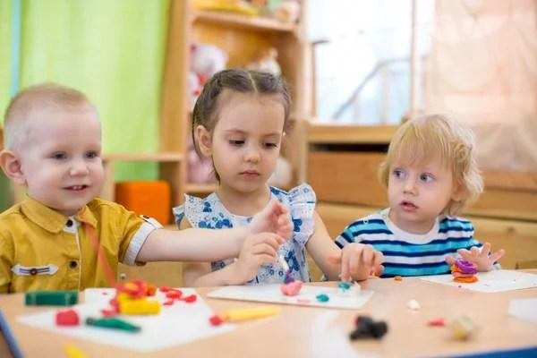 Забавный малыш с открытым ртом ест в детском саду ...