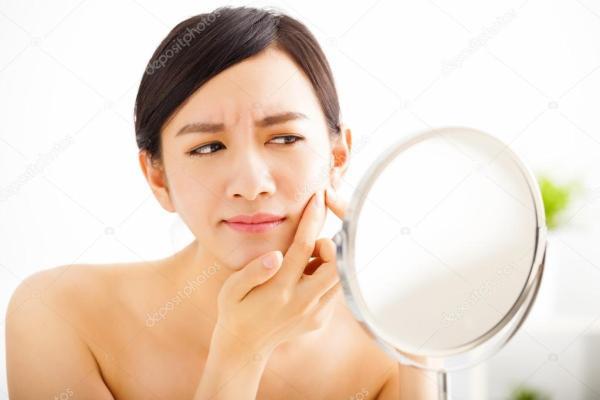 Молодая женщина выжимок прыщ, глядя на зеркало — Стоковое ...