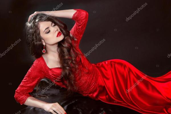 Женщина в красном лежит в темноте. Мода соблазняет девушек ...