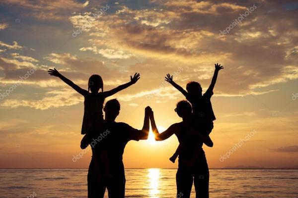 Силуэт счастливой семьи, играющей на пляже на солнце ...
